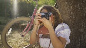 Cute young photographer with curly hair sitting under the tree taking photo using old camera in the garden or park, her. Attractive young photographer with curly stock video