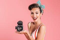 Cute young pin up woman holding camera. Stock Photos