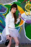 Cute young prostitute brunette girl in white. By a graffiti wall Stock Images