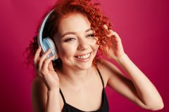Cute young redhead girl in big headphones close up portrait in S. Cute young redhead girl in big headphones happy smiling. close up portrait in Studio on red Royalty Free Stock Photography
