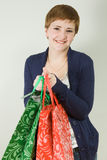 Cute young redhead woman holding shopping bags Stock Photo