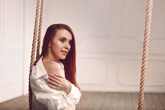 Cute young redhead woman with long hair sitting on swing in man`s shirt. Long socks and white lingerie stock photography