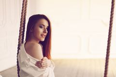 Cute young redhead woman with long hair sitting on swing in man`s shirt. Long socks and white lingerie royalty free stock photos