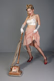 Cute young retro housewife with vacuum cleaner Stock Photos