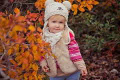 Cute young russian baby girl stylish dressed in warm white fur handmade jacket blue jeans boots and hooked hat teddy bear posing i. N autumn colorful forest Stock Photos