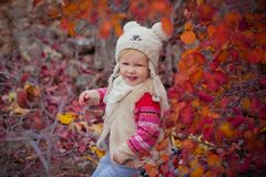 Cute young russian baby girl stylish dressed in warm white fur handmade jacket blue jeans boots and hooked hat teddy bear posing i. N autumn colorful forest Royalty Free Stock Photo
