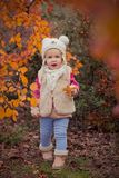 Cute young russian baby girl stylish dressed in warm white fur handmade jacket blue jeans boots and hooked hat teddy bear posing i. N autumn colorful forest Stock Photo