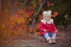 Cute young russian girl stylish dressed in warm red handmade jacket blue jeans boots and hooked hat teddy bear posing in autumn co. Lorful forest pathway Face Stock Photo