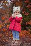 Cute young russian girl stylish dressed in warm red handmade jacket blue jeans boots and hooked hat teddy bear posing in autumn co. Lorful forest pathway Face Stock Photos