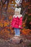 Cute young russian girl stylish dressed in warm red handmade jacket blue jeans boots and hooked hat teddy bear posing in autumn co. Lorful forest pathway Face Royalty Free Stock Photography