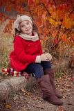 Cute young russian girl stylish dressed in warm red handmade jacket blue jeans boots and hooked headband scarf posing in autumn co royalty free stock image