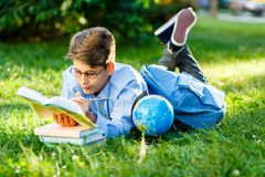 Cute, young schoolboy in round glasses and blue shirt lies on the grass and holds a book in his hands, reads in the park. royalty free stock image