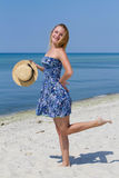 Cute young girl with a hat, in blue dress posing on the beach, sea background. Freedom and fun concept Stock Photo