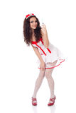 Cute young sexy nurse. Full body shot of a sexy beautiful young nurse wearing red high heels shoes holding a syringe on isolated white background. High Royalty Free Stock Photos