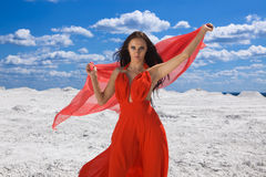 Cute young sexy woman in red dress on the snow. And summer Stock Image