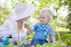 Cute Young Sister Helps Her Brother with Easter Eggs Outside Stock Images