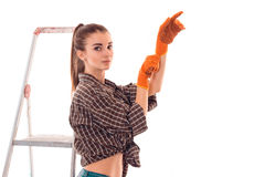 Cute young slim builder girl makes renovations in gloves isolated on white background Stock Photos
