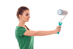 Cute young slim builder girl makes renovations with paint roller isolated on white background Stock Photos