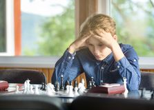 Cute young smart boy in plays chess on the training before the tournament. Hand makes a move on chessboard. Chess summer camp. royalty free stock photography