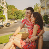 Cute young smiling couple in love laughing hugging, sitting outdoors at green city street, summertime Stock Image