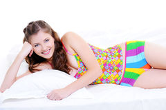 Cute young smiling girl lying down on bed Stock Photos