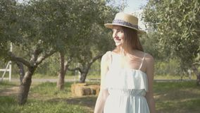 Cute young smiling woman in straw hat and long white dress walking through the green summer garden. Carefree rural life. Attractive young smiling woman in a stock video footage