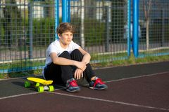 Cute young sport boy with yellow skateboard. He has a good time on his free time on weekend, holidays on sports ground. royalty free stock photography