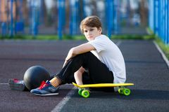 Cute young sport boy with yellow skateboard. He has a good time on his free time on weekend, holidays on sports ground. royalty free stock images