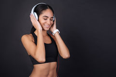 Cute young sportswoman relaxing with music. Listen to music. Happy relaxed brunette keeping her eyes closed while listening music in headphones standing in semi Stock Photos