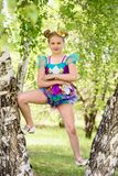 Cute young sporty blond girl standing between two birch trees, wears colorfull sport swimsuit and gold bowler hat. In sunny day royalty free stock photography