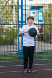 Cute young sporty boy in white t shirt plays basketball on his free time, holidays, summer day on the sports ground. Sport stock image