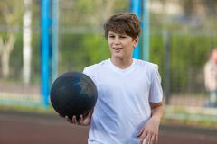 Cute young sporty boy in white t shirt plays basketball on his free time, holidays, summer day on the sports ground. Sport royalty free stock image
