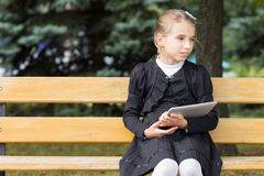Cute young student girl with tablet sitting in the park Royalty Free Stock Photography