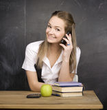 Cute young student near blackboard with copy book calculator pen, copy space Royalty Free Stock Photo