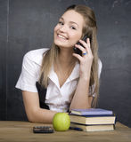 Cute young student near blackboard with copy book calculator pen, copy space Royalty Free Stock Images