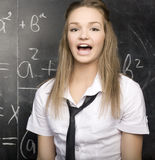Cute young student near blackboard with copy book calculator pen, copy space Stock Images