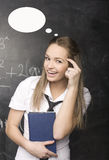 Cute young student near blackboard with copy book calculator pen, copy space Royalty Free Stock Photos