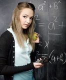 Cute young student near blackboard with copy book calculator pen, copy space Stock Photo