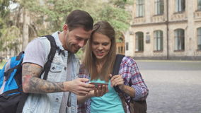 Students watch images on smartphone on campus. Cute young students watching images on smartphone on campus. Handsome brunette man holding cellphone in his hands stock video footage