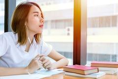 Cute young teen Asian university reading book in library. Cute young teen Asian university girl in uniform reading book in library stock photos