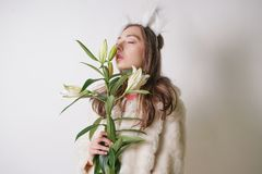 Cute young teen girl standing in a winter warm fur coat and cat furry ears on her head, she holds a branch of fresh lilies. woman. In winter clothes with a royalty free stock image