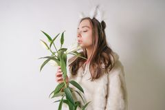 Cute young teen girl standing in a winter warm fur coat and cat furry ears on her head, she holds a branch of fresh lilies. woman. In winter clothes with a stock photo
