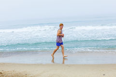Cute young teenage boy joging at the empty beach Stock Photo
