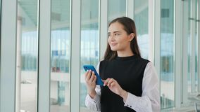 Cute young traveler woman or college student using mobile phone call at airport terminal with luggage. Study or travel. Cute young woman or college student using stock video footage