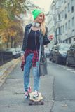 Cute young urban woman using a skate board Royalty Free Stock Photography