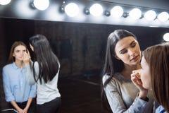 Cute young visagiste applying makeup Stock Image