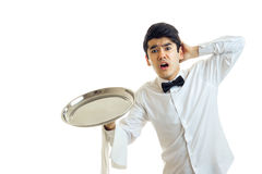 Cute young waiter holding a tray of empty with one hand and the second hand clutched his head. Isolated on white background Royalty Free Stock Images