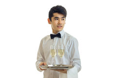 Cute young waiter stands unscrewing my head to the side and holding a tray with glasses of champagne Royalty Free Stock Photo
