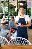 Waiter green white leaves coffee cup portrait young male barista service coffee customer cafe apron. A cute young waiter in a white T-shirt and a blue apron Stock Images