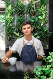 Waiter green white leaves coffee cup portrait young male barista service coffee customer cafe apron st Patrick day. A cute young waiter in a white T-shirt and a Stock Photography
